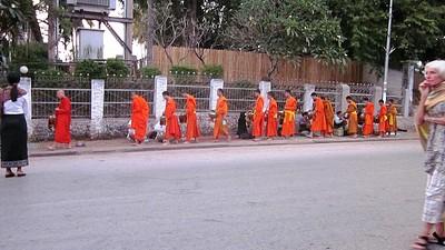 נזירים עוברים בין התושבים לקבל מזון ב6:00