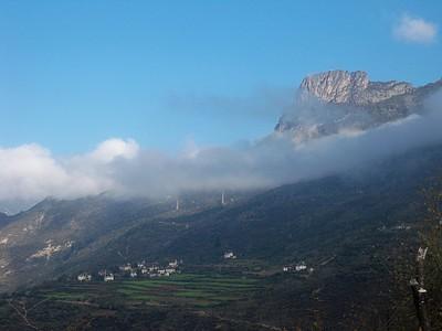הפסגה המרובעת (המחודדת מסתתרת מאחורי העננים בצד שמאל). הדברים האלה בכפרים הם לא עמודי חשמל, דרך אגב, אלה מגדלי אבן עתיקים.