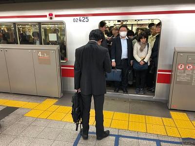 אמצע הלילה והרכבת התחתית בטוקיו מלאה אנשים בחליפות