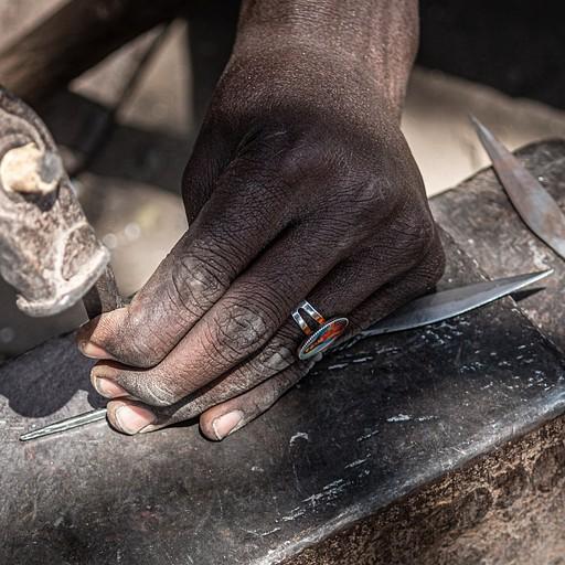 אחד הגברים מראה לנו איך הוא מכין ראש חץ. חדי העין יזהו את ישו בטבעת. קישוט יפה או הופעה לתיירים?