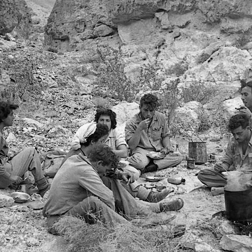 ארוחת צהרים במדבר, שנות ה-50 (ניתן לראות את האוכל, פח לבישול על המדורה ופח המים מאחור). צילום: עזריה אלון, באדיבות משפחת אלון, בית השיטה
