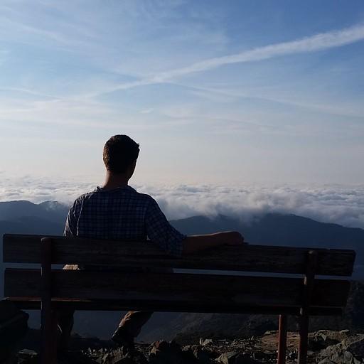 ספסל למנוחה על פסגת הר בדרך, הנוף מזמין להישאר לשבת.