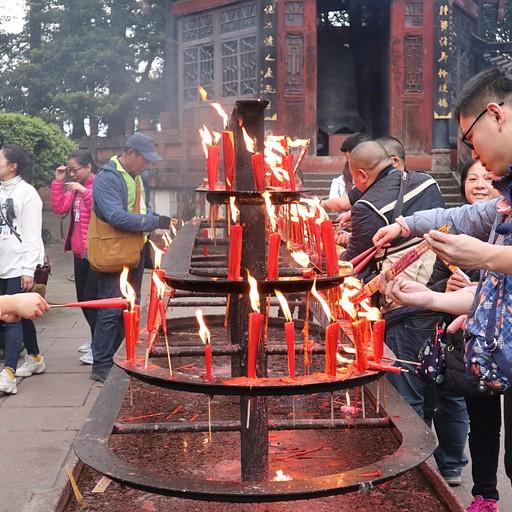 אנשים מדליקים נרות בכניסה למקדשים
