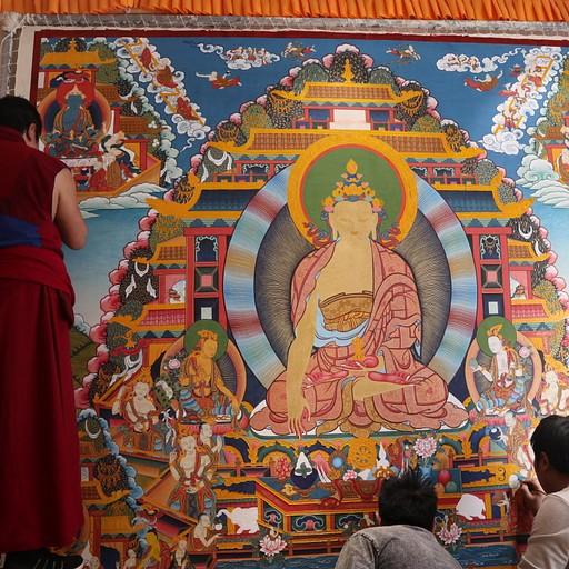 נזיר ושני מקומיים מציירים ציור קיר שייתלה במקדשים