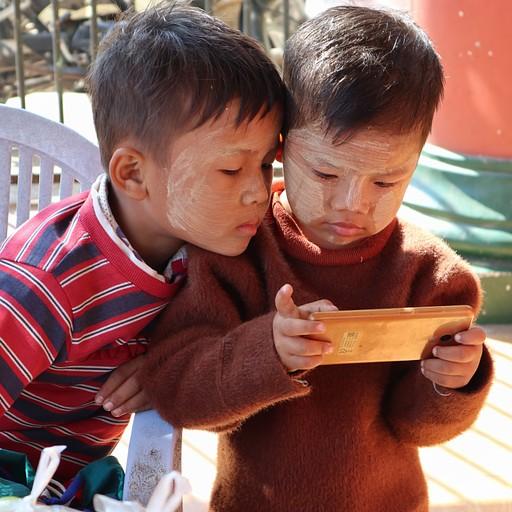ילדים בורמזים משחקים בטלפון בכניסה לאחד המקדשים