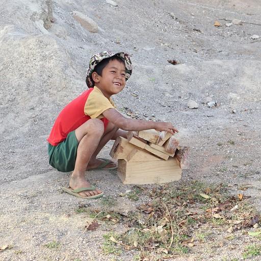 בכפר בו ישנו הילדים משחקים באתר בנייה עם קוביות עץ שנשארו מהבנייה