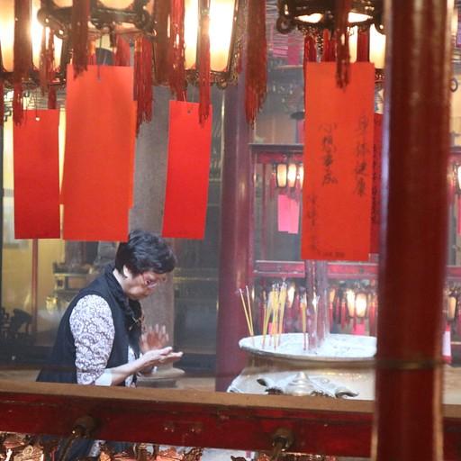 אישה מפתללת במקדש Yau Ma Tei Tin Hau Temple