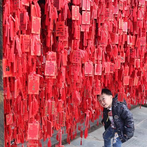 באחד המקדשים, תולים סרטים אדומים עם ברכות וכיתוב בסינית