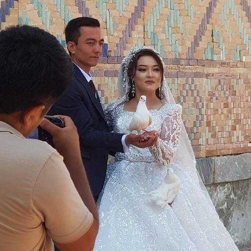 זוג מצטלם על רקע קיר הרגיסטן. היונים הלבנות נפוצות מאוד לטובת צילומי חתונה.