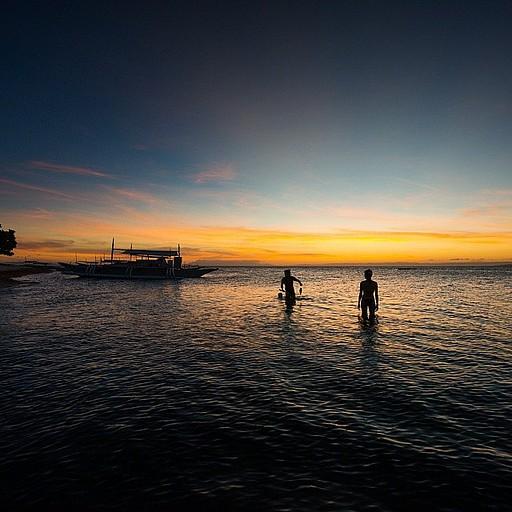 דייג מקומי יוצא מהמים בשקיעה עם דג שתפס בצלילה חופשית עם סכין