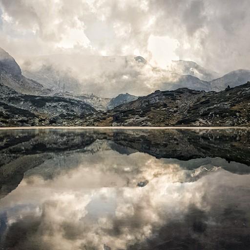 השמש שוקעת ומשתקפת יחד עם ההרים על האגם השקט