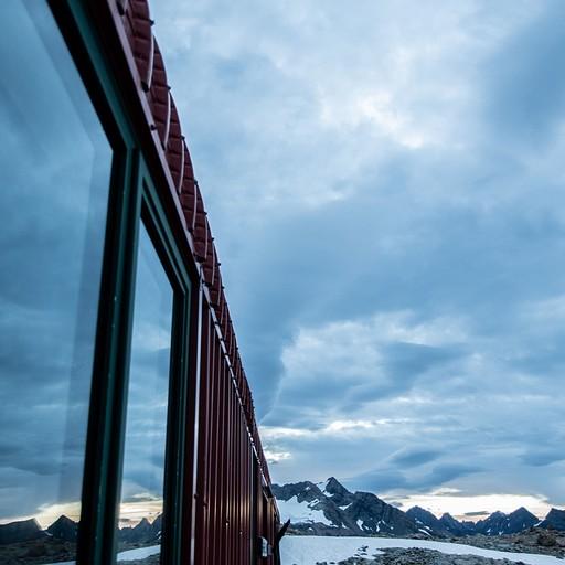 השתקפות ההרים בחלונות הבקתה