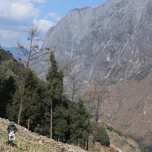 הכול פורח וירוק מול ההרים הסלעיים, בכפר של גסטהאוס אמצע הדרך